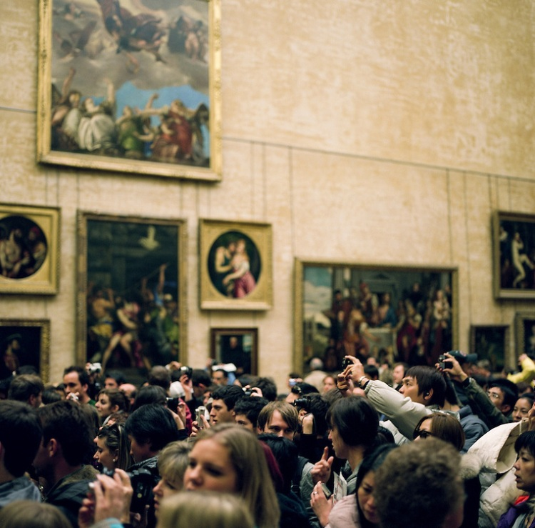 Tourists swarm around the Mona Lisa at the Louvre Museum in Pari